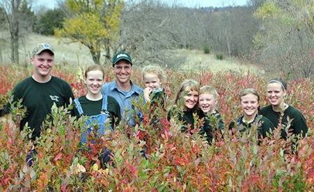 Wiley family in nursery full of large blueberry plants for sale